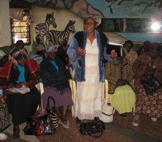 A grandmother in Kenya tells her story to a room of grandmothers.