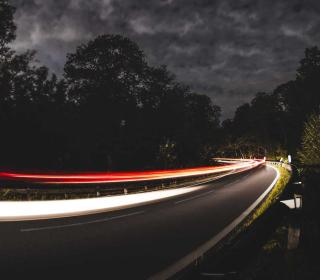 In a long exposure photo, headlights and taillights of cars blur as they rush around a corner at night.