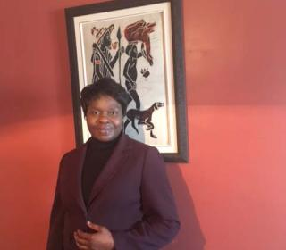 The Rev. Marie-Claude Manga, standing in front of an artwork, dressed in a brown jacket.