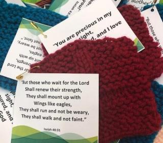 Image: Printed Bible verses, each pinned to a small knitted square, lying on a table in the GC43 chaplaincy room