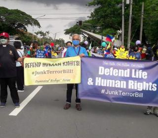 People on street hold up banners protesting human rights abuses in the Philippines