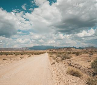 A dirt road running straight through the sparse desert, with dramatic clouds overhead.