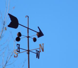 Metal weather vane made up of an arrow and north, south, east, west arrows against a blue sky