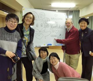 Kyofukai staff (four Japanese women) and United Church representatives (a woman and man) gather about an easel for a photo.