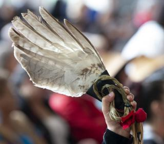 Photo of an eagle feather held up during ceremonies marking the release of the Missing and Murdered Indigenous Women report in Gatineau,  June 3, 2019