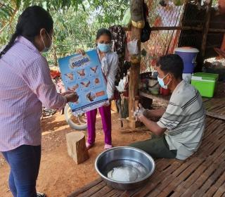 Two women wearing masks hold a sign showing proper hand hygiene during COVID-19 while a seated man wearing a mask demonstrates handwashing.
