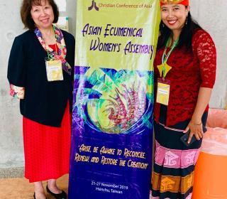 "Author Kim Uyede-Kai from the United Church stands with Rev. Ester Damaris Wolla Wunga from Indonesia stand with an assembly banner. Both women are of Asian background, but the ""traditional dresses"" they are wearing reflect their different cultures."