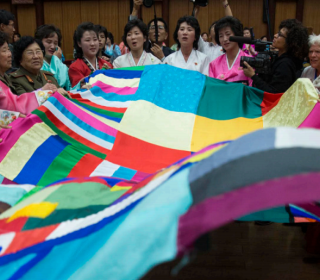 Women mobilize for peace in Korea, gathered around a large multi-coloured fabic during a demonstration.