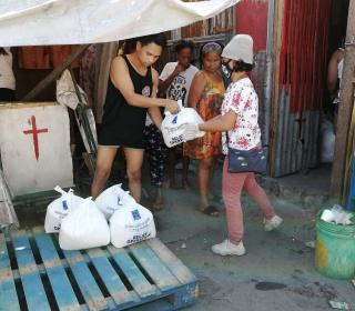 A woman wearing a mask distributes plastic bags containing food and health supplies to urban families in the Philippines.