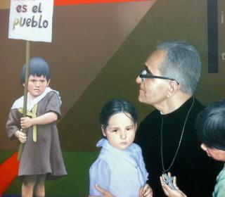 "A detail from a mural at Monseñor Óscar Arnulfo Romero International Airport in El Salvador, showing Archbishop Oscar Romero and several children, one holding a sign that says ""Mi amor es el pueblo"" (""My love is the people."")"