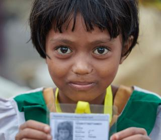 A Rohingya girl, having just crossed the border from Myanmar, shows her new identity card that she was given by United Nations workers in a refugee camp in Bangladesh.