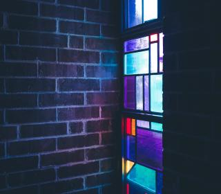 Stained glass beside brick wall