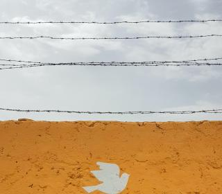 A wall painted with a dove topped by barbed wire against a cloudy sky.