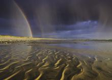 A rainbow seen from a beach while storm clouds swirl overhead.