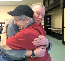 Two participants at 1JustCity, an older White woman and White man, share a hug.