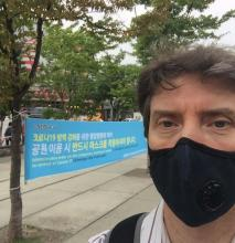 The author, John Egger, wears a pandemic face mask as he takes a selfie before a sign written in Korean in Seoul, Korea.