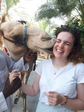 A young woman gets a big sloppy kiss from a camel on the side of her face and squirms.