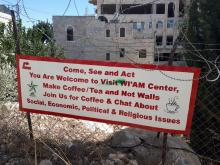 "A welcome sign for Wi'am Center on a barbed-wire fence in Palestine, with the message, ""Make Coffee/Tea and Not Walls."""