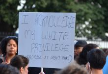 "A white woman holds a sign that says, ""I acknowledge my white privilege"" during a protest."