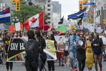 Black Lives Matter supporters march at Toronto Pride 2016, beneath a large Canadian flag and flags representing the Trans movement.