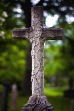 A stone cross standing outside, in front of the a background of green trees.