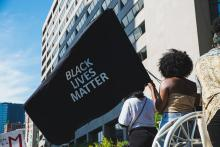 A Black woman seen from behind while holding a large Black Lives Matter flag during a march in downtown Toronto.