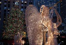 A sculpture of an angel blowing a horn, standing in front of a Christmas tree with multi-coloured lights.