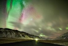 Yellow, green, and pink aurora shines above a isolated road at night.