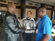 Three Black male clergy great each other at the United Church Black Clergy Gathering.