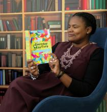"Lenten book editor Alydia Smith, dressed in a long purple dress and detailed necklace, sits in a large comfy to read a copy of the book ""Everyday Skeptics."""