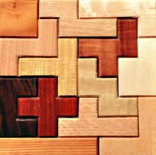 A puzzle of wooden pieces, each a different colour and angular shape, including one dark brown piece in the shape of a cross.