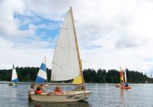 A small sailboat being piloted by two children in lifejackets in a lovely lake surrounded by forest. In the background are a number of similar boats piloted by camp kids.