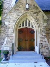 Dark red arch-shaped doors of a stone church.