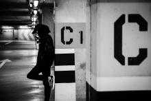 In this black and white photograph, a young man in a hoodie looks pensive while he leans against the wall in a subway station.