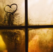 A cross and heart image is seen in a back-lit window with yellow and brown tones.