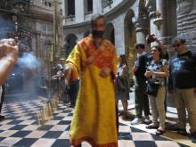 An Eastern Orthodox priest in an orange robe swings a censor in The Church of the Holy Sepulchre in Jerusalem.