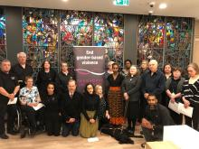 This photo shows a group of 19 diverse people of differing backgrounds and types of abilities in front of a large multi-coloured stained glass. Included in the group are those who participated in the conversation on inclusion. conversation