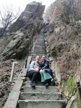 Two young women sit together on the stone staircase of a huge mountain in China.