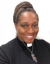 A portrait of Rev. Dr. Karen Georgia Thompson, a Black woman with beautiful braids atop her head in a bun, wearing a clergy collar and a metal owl pendant.