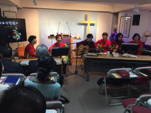 A small group of Korean women, wearing festive red sweaters, lead worship at a church in South Korea.