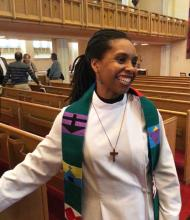 Rev. B. Maya Douglas, a Black woman, stands smiling among the pews of her church, wearing an alb and colourful embroidered stole.