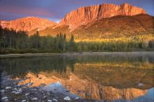 A golden sun shines on Mount John Laurie, known as Yamnuska, in Alberta.
