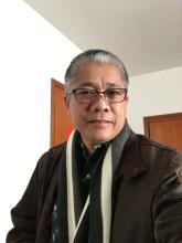 The author, Noel A. Suministrado, a Filipino man with short dark hair with streaks of grey. Wearing glasses and a scarf.