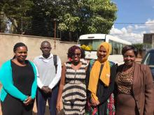 Four women and one man pose together in a Nairobi street. All are well dressed and workers for refugee assistance program.