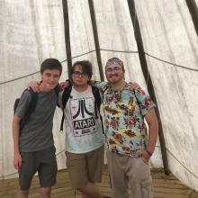 Three young men from the GC43 Pilgrims group pose together in a tepee while learning about the First Nations in the Saskatchewan area.