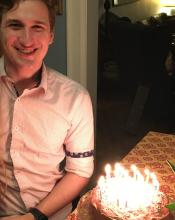 A young white man standing in a door frame, illuminated by the candles on the cake for his birthday.