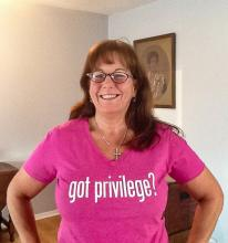 "The author, Karen Orlandi, wears a pink shirt with the words, ""Got Privilege?"" printed on the front in bold letters."