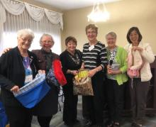 Author YoonOk Shin and the United Church Women of Alberta and Northwest Conference pose for a group shot with the shopping bags they sewed.