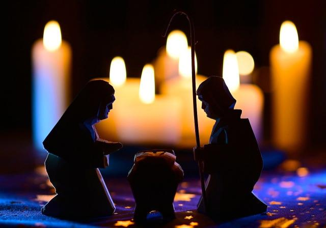 The statues of a Nativity scene are silhouetted by a background of candles.