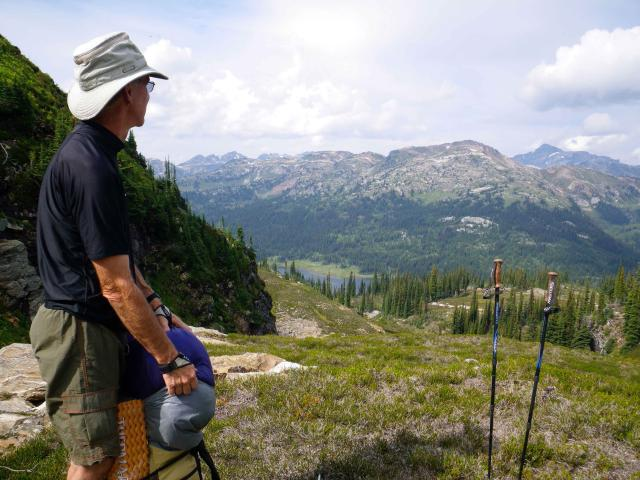Bill on a mountain, looking over the valley and the mountains beyond